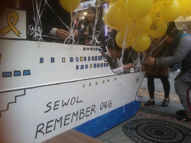 시민들이 세월호 인양을 바라는 글이 적힌 풍선을 세월호 모형의 배에 매달고 있다.