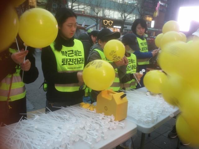 자원봉사자들이 세월호 인양을 염원하는 풍선을 시민들에게 나눠주고 있다.