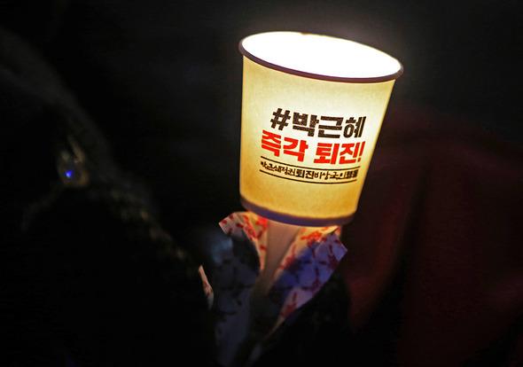 기온이 올겨울 들어 '최강 한파'를 기록한 1월14일 저녁 '박근혜 정권 퇴진 비상시국행동'이 서울 광화문 광장에서 연 '즉각퇴진, 조기탄핵, 공작정치 주범 및 재벌총수 구속 12차 범국민행동의 날' 촛불집회에서 한 시민이 손난로를 감싼 채 촛불을 들고 있다. 강창광 기자 chang@hani.co.kr