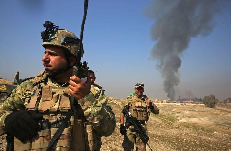 이라크 정부군이 이슬람국가(IS)가 점령했던 모술 공항을 탈환한 23일 병사들 뒤로 멀리 모술 공항에서 폭탄이 터진 연기가 피어오르고 있다. 모술/AFP 연합뉴스