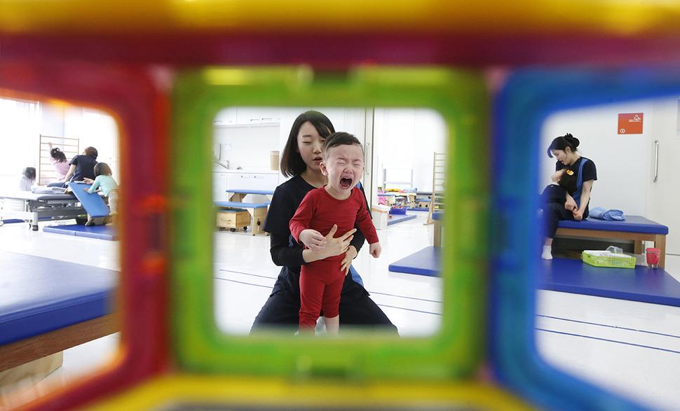 장준혁(2)군이 지난 9일 재활치료센터에서 엄마를 찾으며 우는 모습이 알록달록한 교구 너머로 보이고 있다. 준혁이는 생후 4개월 때 걸린 뇌수막염으로 뇌병변 장애를 얻었다.