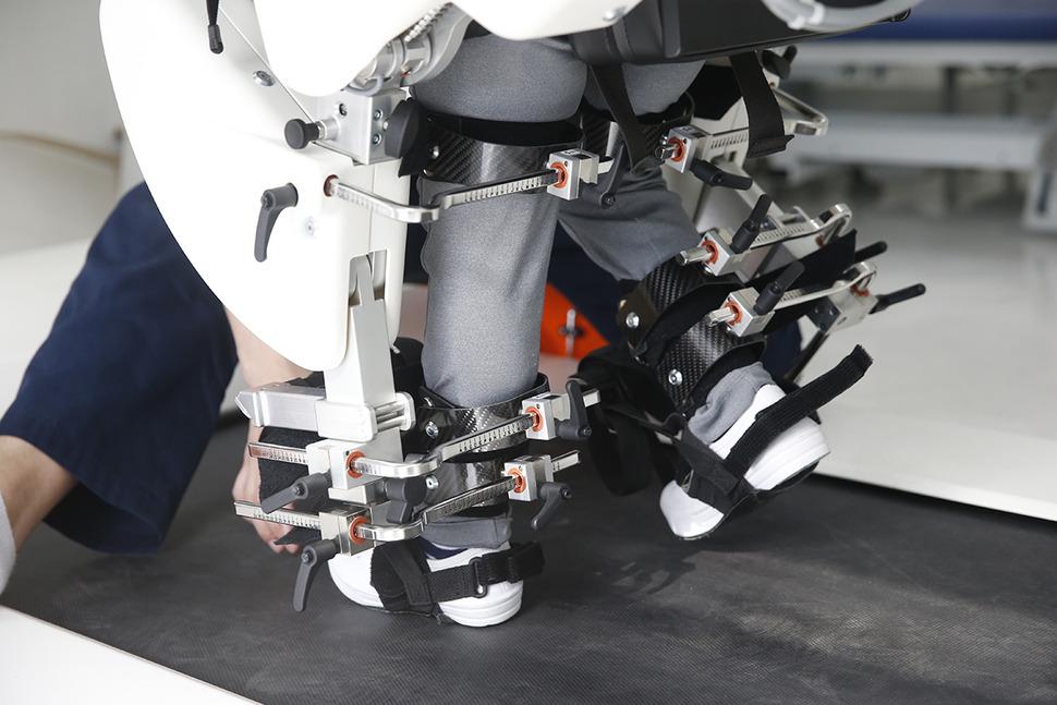한 어린이가 로봇치료실에서 기계의 도움으로 걷기 훈련을 받고 있다.
