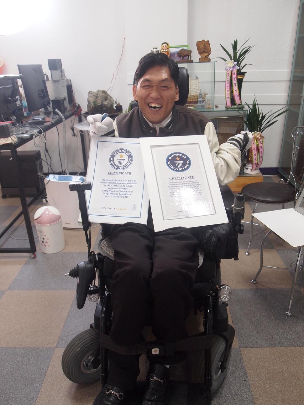 선천성 뇌성마비 장애를 앓고 있는 최창현 대구장애인차별감시연대 대표가 자신이 세운 기네스 신기록 증명서 2장을 들고 환하게 웃고 있다.  최창현 제공