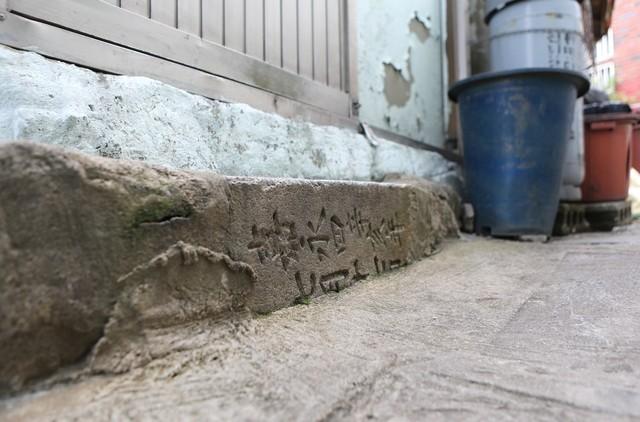 아미동 골목 한 주택 문앞의 디딤돌. 묘지석이다.