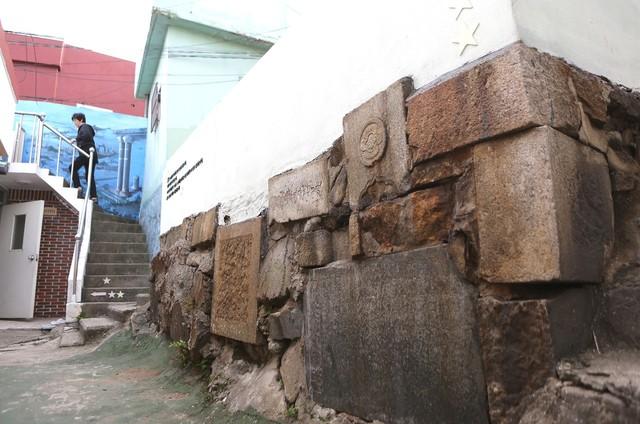 부산 서구 아미동 '비석문화마을' 골목길의 축대. 비석·상석 등 묘지에 쓰였던 다양한 석재들이 박혀 있다.