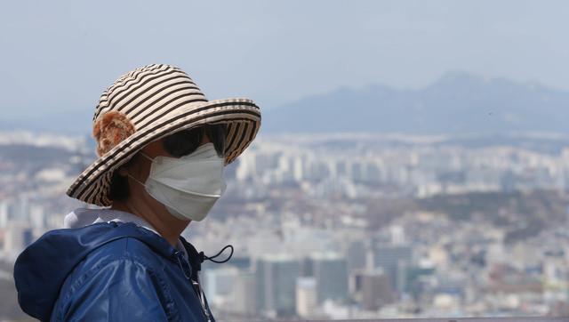 서울 남산에 오른 시민이 미세먼지에 대비해 마스크를 쓰고 도심을 내려다 보고 있다. 신소영 기자 viator@hani.co.kr