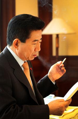 담배를 피우며 서류를 검토하고 있는 노무현 전 대통령의 생전 모습.