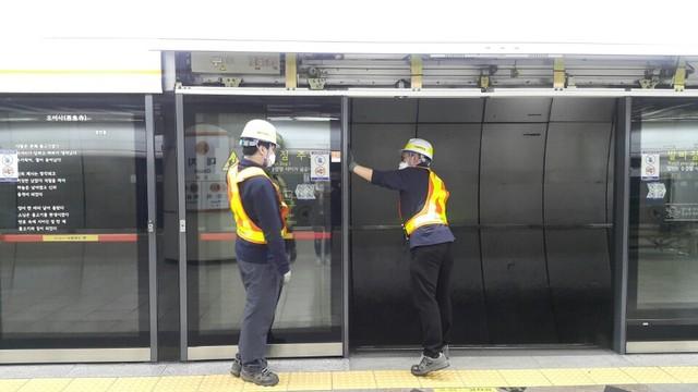 21일 새벽 서울메트로 3호선 대치역 선로 안에서 선릉 PSD 관리반 직원들이 2인1조로 고장난 스크린도어 센서 교체 작업을 하고 있다.