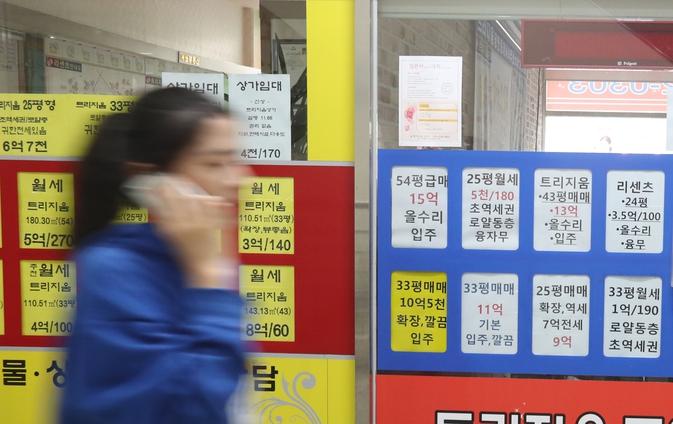 서울 송파구 잠실동의 한 공인중개사무소 앞에 빼곡히 붙은 아파트 시세표 앞을 한 시민이 지나가고 있다. 연합뉴스