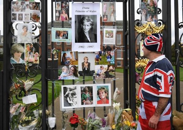 지난 29일 영국 런던의 켄징턴궁 문 앞에 추모객들이 붙여놓은 고 다이애나 왕세자비 사진을 한 시민이 바라보고 있다. 런던/EPA 연합뉴스