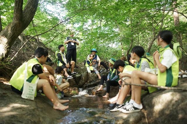제10회 숲사랑소년단 전국대회에 참가한 학생들이 자연 속에서 숲해설가의 설명을 듣고 있다. 숲사랑소년단 제공