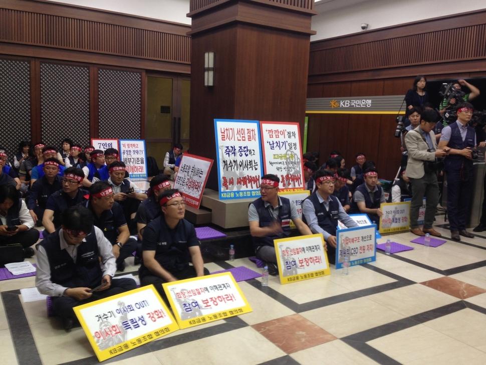 7개 계열사 연합체인 케이비(KB)금융그룹 노동조합협의회 노조원들이 14일 저녁 지주 회장 최종후보군을 선정하는 확대지배구조위원회가 열리는 서울 케이금융 명동본점에서 연좌 농성을 벌이고 있다