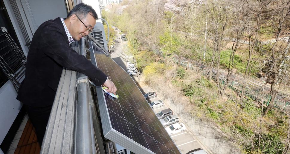 한 서울시민이 자신이 거주하는 아파트 발코니에 소규모 태양전지판을 설치한 뒤 살펴보고 있다.                       김경호 선임기자 jijae@hani.co.kr