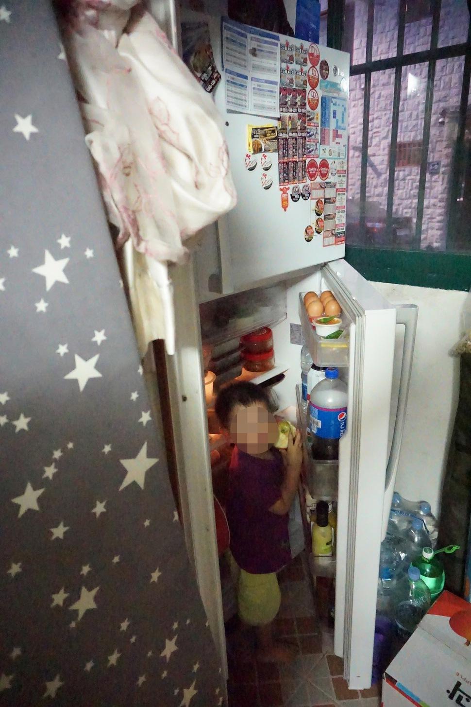 윤성학·권경인씨 부부의 막내 아들이 베란다에 놓인 냉장고 문을 열고 사과를 꺼내 먹고 있다. 박기용 기자
