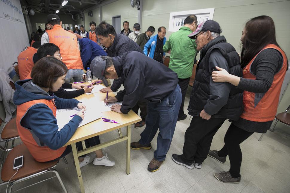 31일 오전 서울 중구 동자동 무료급식소 '따스한 채움터'에서 지역주민들이 예방접종에 앞서 예진표를 작성하고 있다. 김성광 기자