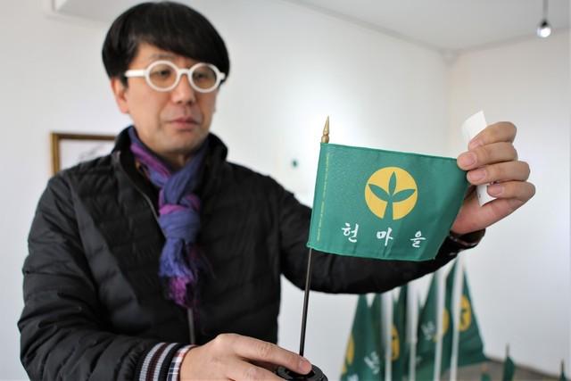 안덕벌 '동네 예술가' 조송주씨가 '헌마을 기'를 보여주며 '헌마을 재생'의 뜻을 밝히고 있다.