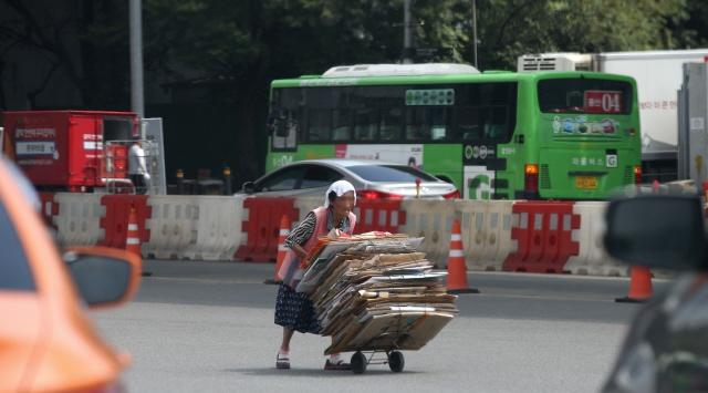 지난여름 서울 서부역 도로에서 한 할머니가 한낮의 땡볕을 손수건 한장으로 가린 채 폐지를 고물상으로 가지고 가고 있다. 김봉규 선임기자 bong9@hani.co.kr