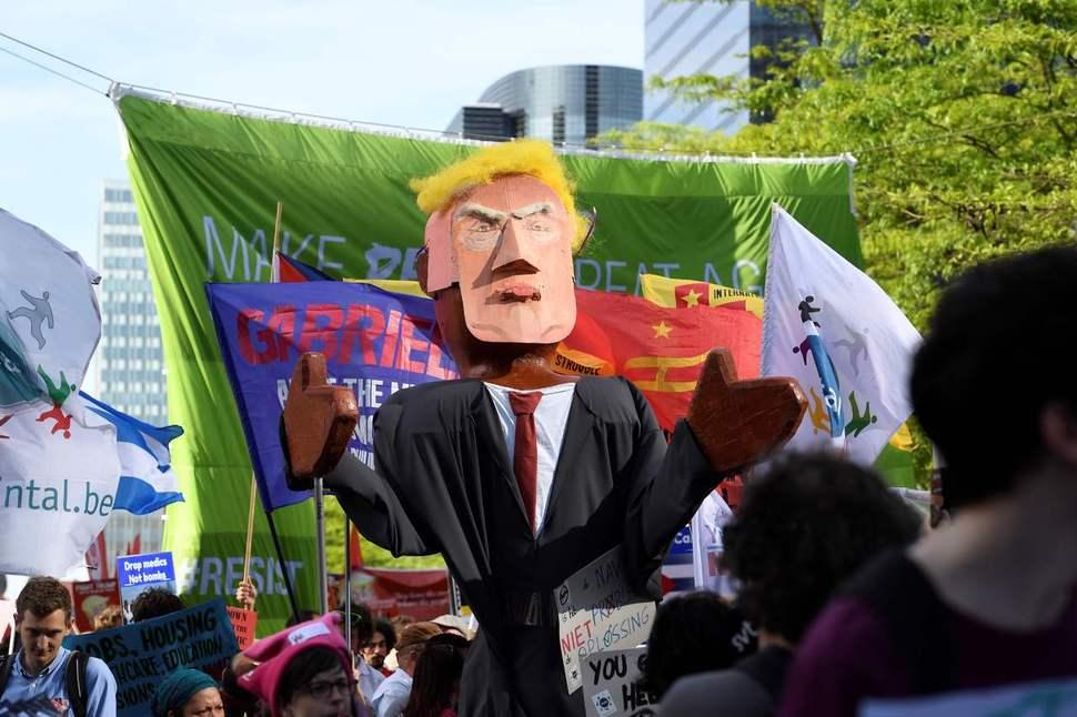 북대서양조약기구(나토) 정상회의를 하루 앞둔 5월24일(현지시각) 벨기에 브뤼셀에서 도널드 트럼프 미국 대통령을 비판하는 집회가 열린 가운데 시민들이 트럼프를 묘사한 모형을 옮기고 있다. 브뤼셀/AFP 연합뉴스