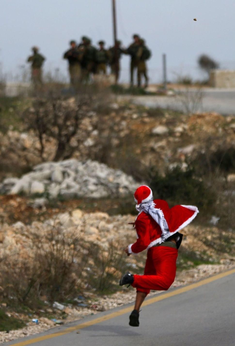 도널드 트럼프의 '예루살렘 수도' 선언 이후 예루살렘을 둘러싼 긴장이 고조된 가운데, 지난 19일(현지시각) 산타클로스 복장을 한 팔레스타인 시위자가 예루살렘 아타로트 검문소 주변에서 이스라엘군을 향해 돌을 던지고 있다. 예루살렘/AFP 연합뉴스