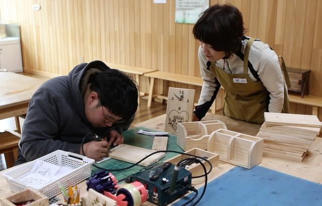 충주 행복숲체험원의 목재문화체험장에서 체험객이 나무판을 이용한 시계를 만들고 있다.