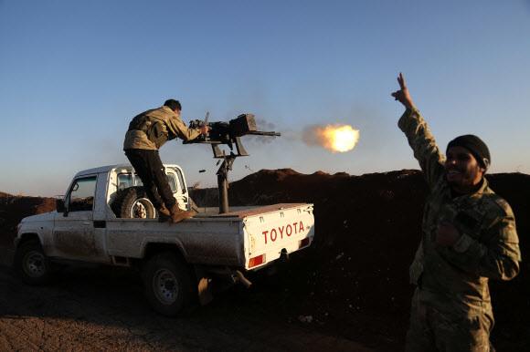 터키의 지원을 받는 시리아 반군 세력인 자유시리아군이 20일 알레포 북부의 탈 말리드에서 쿠르드 인민수비대 쪽을 향해 사격을 가하고 있다. AFP 연합뉴스