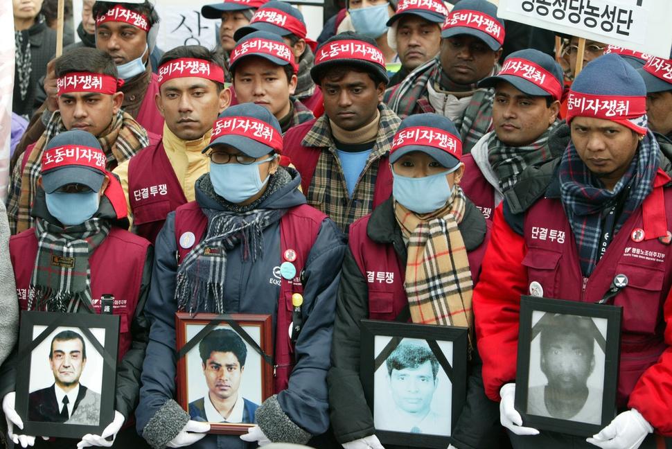 2003년 세계 이주노동자의 날(12월18일) 서울 종로구 종로타워 앞에서 열린 '강제추방으로 죽어간 이주노동자·동포 추모제'에서 이주노동자들이 그해 강제단속 중 사망한 사람들의 영정을 들고 있다. 맨 왼쪽 영정 속 얼굴이 우즈베키스탄인 부르혼. 김진수 <한겨레21> 기자 jsk@hani.co.kr