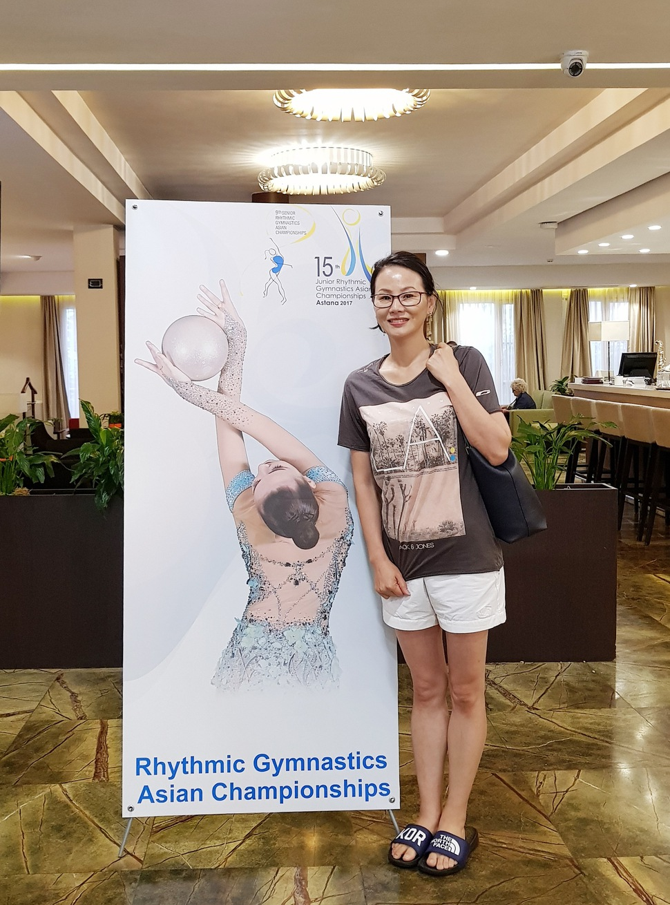 2017년 6월 카자흐스탄 아스타나에서 열린 리듬체조 아시아선수권대회에 참석한 이경희 리듬체조 국가대표 후보선수 전임지도자가 대회를 알리는 표지판 옆에서 포즈를 취하고 있다. 이경희씨 제공