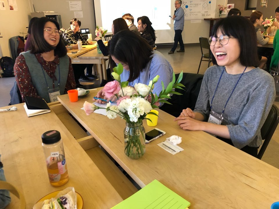 토론에 참여한 참가자들이 대화를 나누며 환하게 웃고 있다.