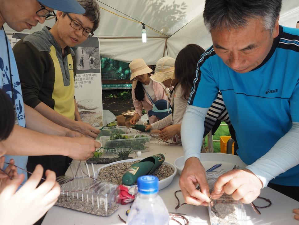 참가자들로부터 인기를 모은 페트병으로 어항 만들기 행사를 벌인 한국민물고기보존협회 회원들.