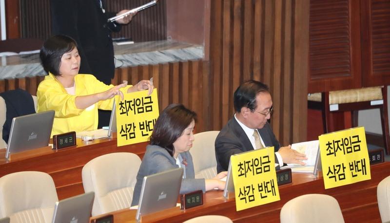 이정미 정의당 대표(왼쪽)가 28일 오후 서울 국회 본회의에서 최저임금 삭감반대 손팻말을 컴퓨터 화면 뒷면에 붙이고 있다. 강창광 기자 chang@hani.co.kr