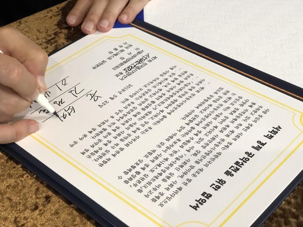 지난달 23일 열린 '2018 서울 사회적경제 지방선거 매니페스토 협약식'에서  한 후보가 '사회적경제 공약실천을 위한 협약서'에 서명하고 있다.