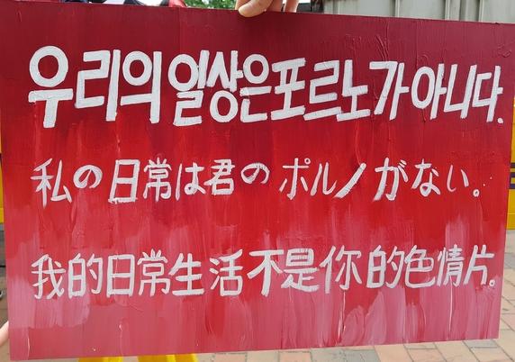 """9일 '불편한 용기'가 주최한 홍대 불법촬영 편파수사 규탄 2차 집회에 참여한 한 여성이 불법촬영을 규탄하는 취지로 """"우리의 일상은 포르노가 아니다""""라고 적힌 손팻말을 들고 있다. 선담은 기자 sun@hani.co.kr"""