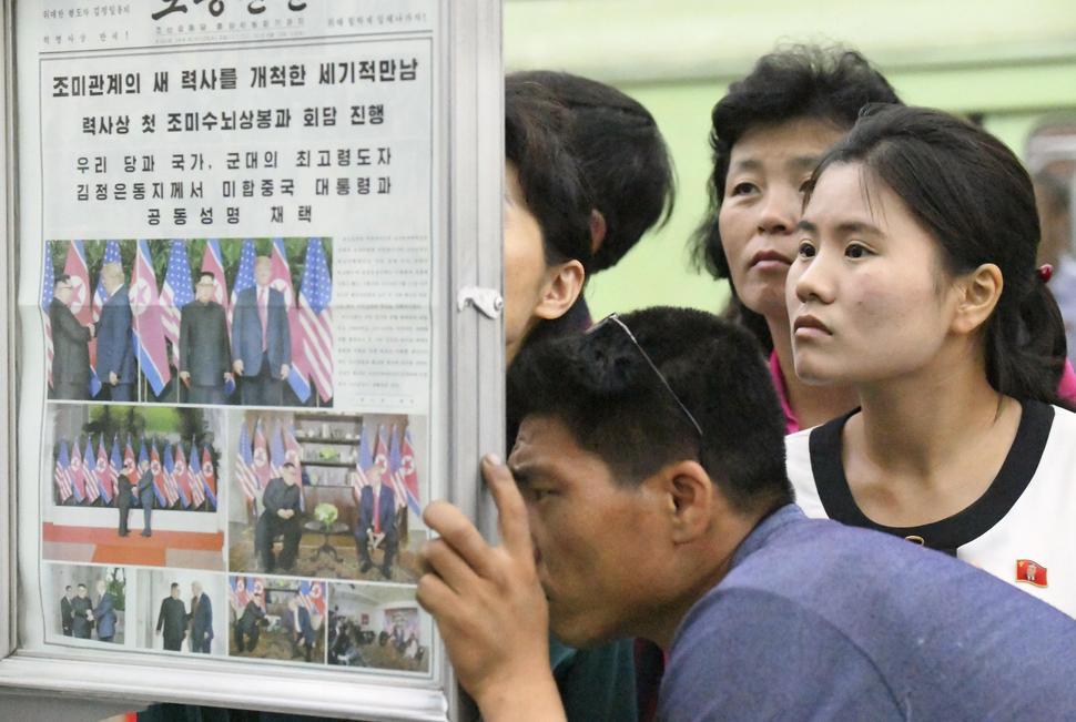 평양 시민들이 13일 시내 지하철역에 비치된 노동신문을 주의 깊게 살펴보고 있다. 13일 노동신문은 북-미 정상회담 소식을 대대적으로 보도했다. 평양/교도 연합뉴스