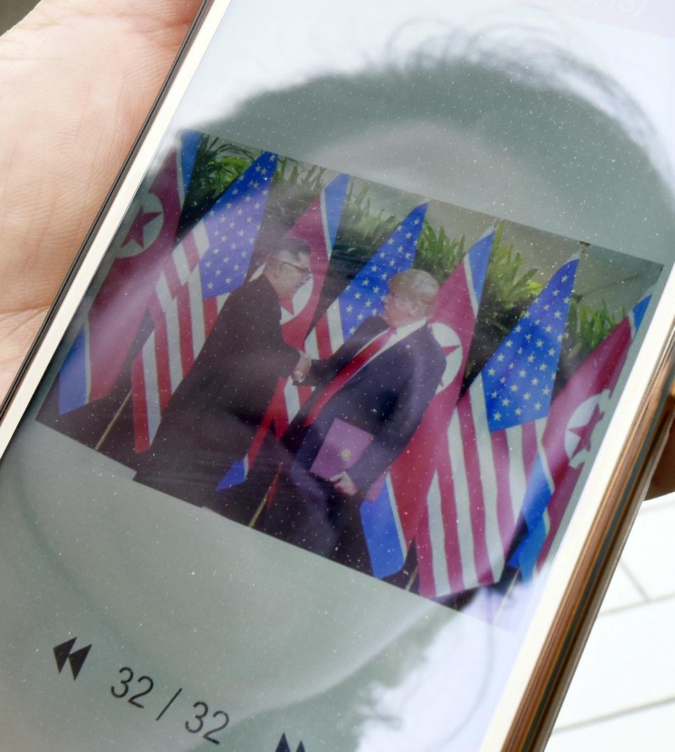 한 평양 시민이 13일 스마트폰으로 북-미 정상회담 관련 뉴스를 확인하고 있다. 평양/교도 연합뉴스