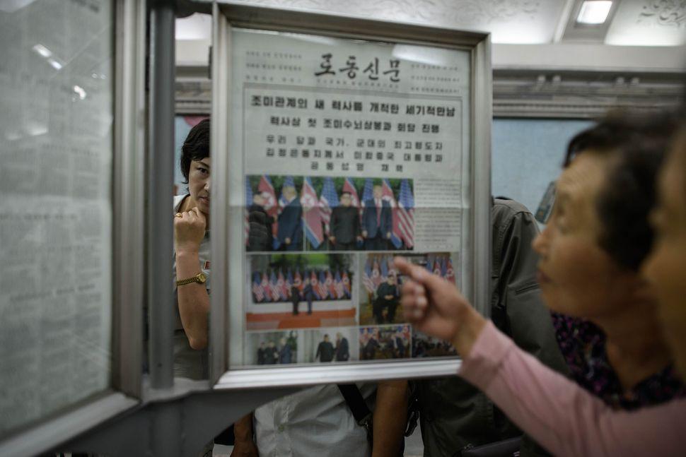 평양 시민들이 13일 시내 지하철역에 비치된 노동신문을 주의 깊게 살펴보고 있다. 13일 노동신문은 북-미 정상회담 소식을 대대적으로 보도했다. 평양/AFP 연합뉴스