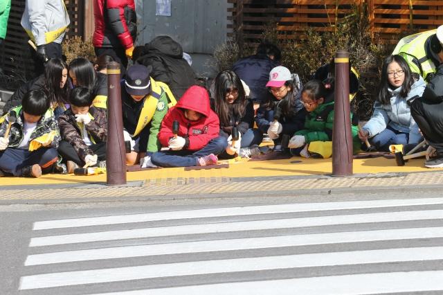 서울의 한 초등학교 어린이와 학부모들이 안전한 통학로 만들기 사업의 하나로 학교 앞에 '옐로카펫'을 설치하고 있다. 김정효 기자 hyopd@hani.co.kr