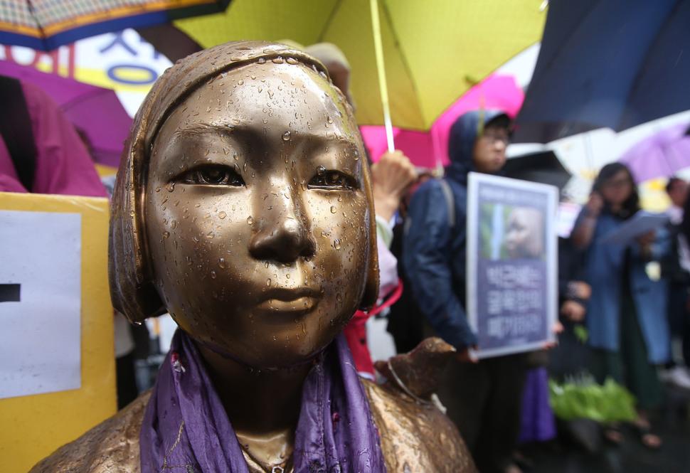 2016년 8월31일 오전 서울 종로구 주한 일본대사관 앞에서 '일본군 성노예제 문제 해결을 위한 정의기억재단'이 개최한 12·28 한-일 합의 강행 규탄 및 정의로운 해결을 촉구하는 기자회견이 열리고 있다. 기자회견 도중 내린 비로 소녀상의 눈가에 빗물이 고여 있다. 신소영 기자 viator@hani.co.kr