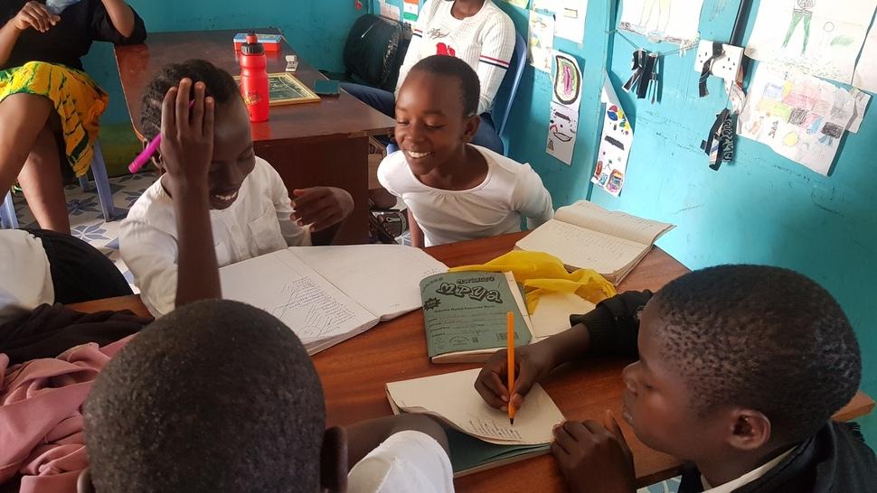 케냐 미고리주 쿠리아의 '미스차나 도서관'에서 진행된 방과후 활동에 참가한 여성청소년들이 영어단어 받아쓰기 시험을 본 뒤 서로 문제를 채점해주며 웃고 있다.