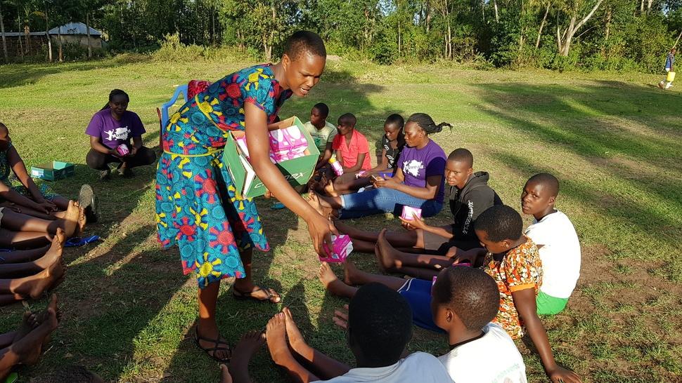 케냐 미고리주 쿠리아 이커리지 마을의 교회 공원에서 '미스차나 쿠리아 임파워먼트'(MEK) 활동가들이 가져간 생리대를 여성청소년들에게 나눠주고 있다.