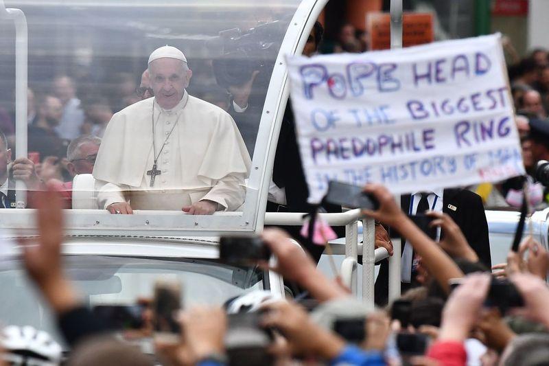 세계가정대회 참석차 아일랜드를 방문한 프란치스코 교황이 지난달 25일 더블린에서 전용차량을 타고 시민들에게 인사하고 있다. 오른쪽엔 가톨릭교회에서 드러난 어린이 성 학대를 항의하는 펼침막이 보인다. 더블린/AFP 연합뉴스