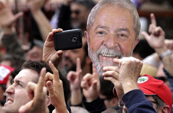 루이스 이나시우 룰라 다 시우바 브라질 전 대통령의 지지자들이 11일 쿠리치바시 연방경찰본부 앞에서 룰라 전 대통령의 얼굴 사진을 들고 집회를 열고 있다. 쿠리치바/AP 연합뉴스