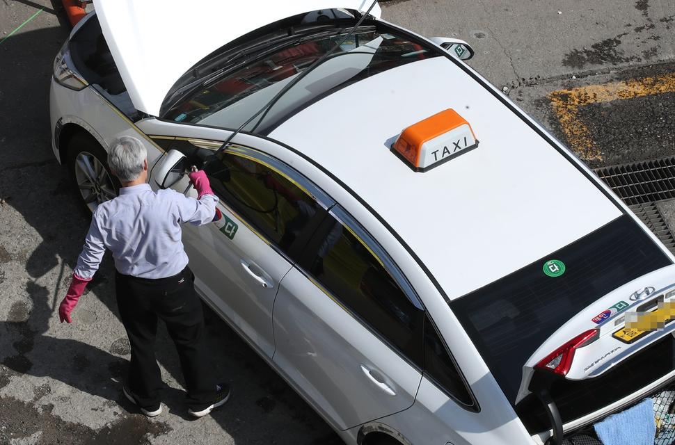 상시 5인 미만 사업장, 육상 운송 등 5개 특례업종은 주 52시간 노동시간 상한제의 적용을 받지 않는다.  서울의 한 액화석유가스(LPG) 충전소에서 택시기사가 세차를 하고 있다. 연합뉴스