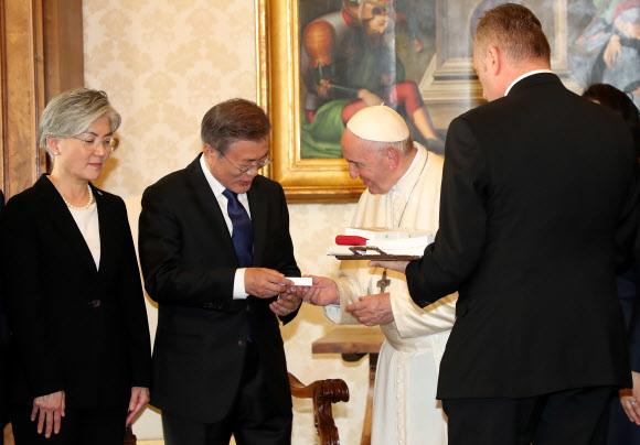 교황청을 공식 방문한 문재인 대통령이 18일 오후 (현지시간) 바티칸 교황청을 방문해 프란치스코 교황과 단독 면담한 뒤 선물을 받고 있다. 연합뉴스