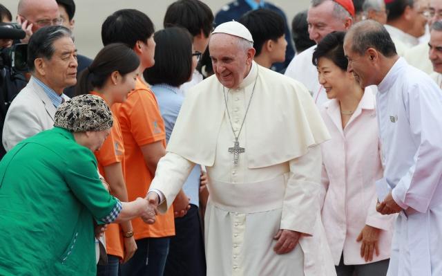 프란치스코 교황이 2014년 8월14일 경기도 성남 서울공항을 통해 입국, 영접 나온 천주교 관계자들과 인사를 나누고 있다. 사진공동취재단.