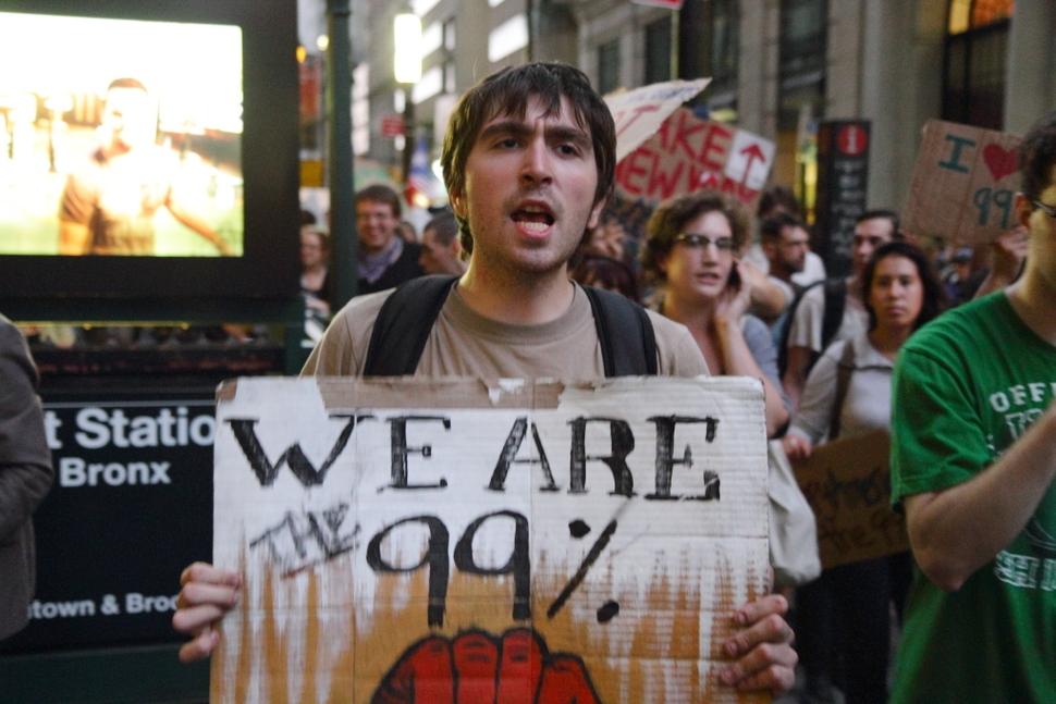 2011년 9월 미국 뉴욕의 금융 중심지 월스트리트에서 극단적인 빈부 격차와 금융자본의 탐욕에 항의해 벌어진 '오큐파이(점령하라) 운동'에 참가한 한 시민이 '우리가 99%다'라고 쓰인 팻말을 들어보이고 있다.   위키미디어 커먼스