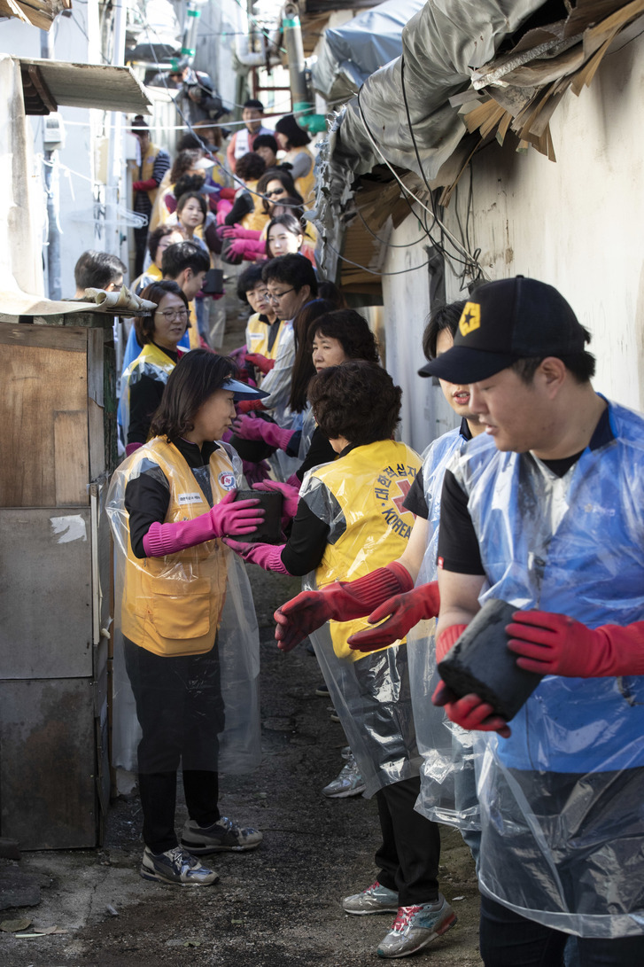 고려아연 임직원과 적십자 봉사자들이 10월 24일 서울 노원구 상계 3동과 4동에 거주하는 취약계층 66세대의 겨울나기를 돕기 위해 줄을 서서 연탄을 나르고 있다.  김성광 기자 flysg2@hani.co.kr