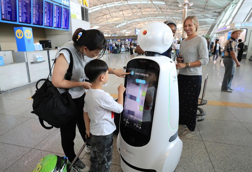 인천국제공항 1터미널 출국장에서 여행객들이 2세대 안내로봇 '에어스타(AIRSTAR)'를 살펴보고 있다.   연합뉴스