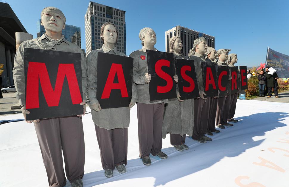 """제주4·3관련 단체 관계자들이 31일 오후 서울 광화문광장에서 제주4·3에 대한 미국의 책임있는 조처를 요구하는 10만인 서명지를 주한 미국대사관에 전달하기 전 행위극을 하고 있다. 이들이 만든 문장은 """"The U.S. must take responsibility for the jeju 4.3 massacre""""(미국은 제주4·3 학살에 대해 책임져야 한다)이다. 김정효 기자 hyopd@hani.co.kr"""