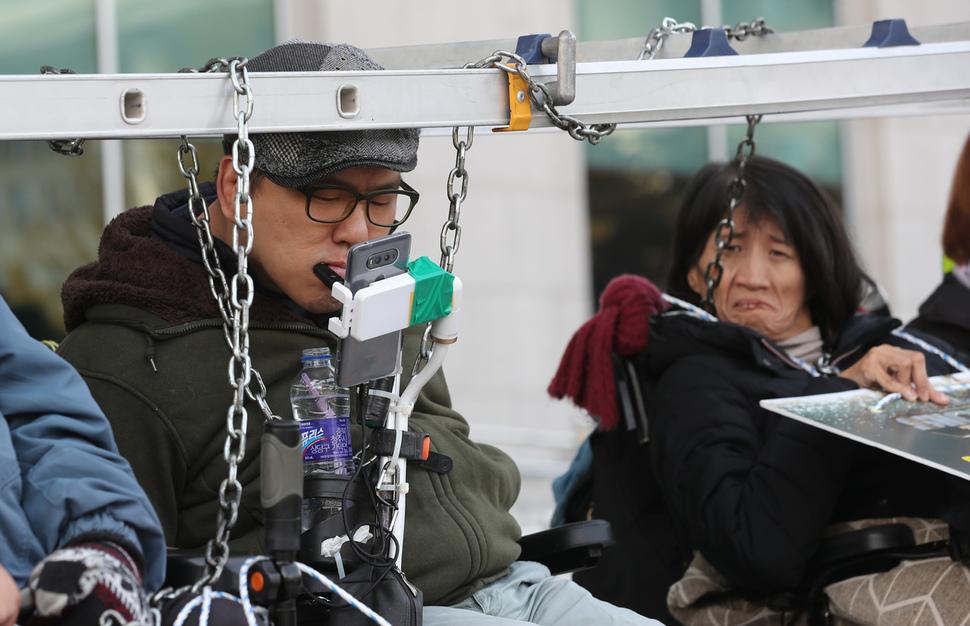 기습 시위를 벌이던 한 장애인이 입으로 핸드폰을 조작하고 있다. 강창광 기자