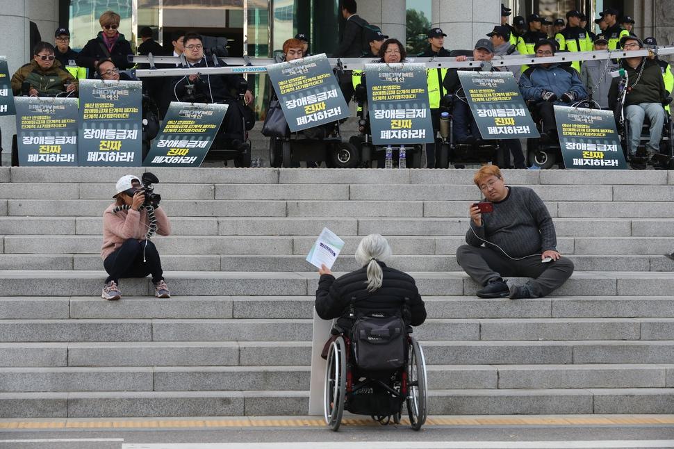 국회의원회관 앞에서 기습시위를 벌이던 장애인들이 더불어민주당 조정식 예결위 간사와 만나고 돌아온 대표자의 설명을 듣고 있다. 강창광 기자